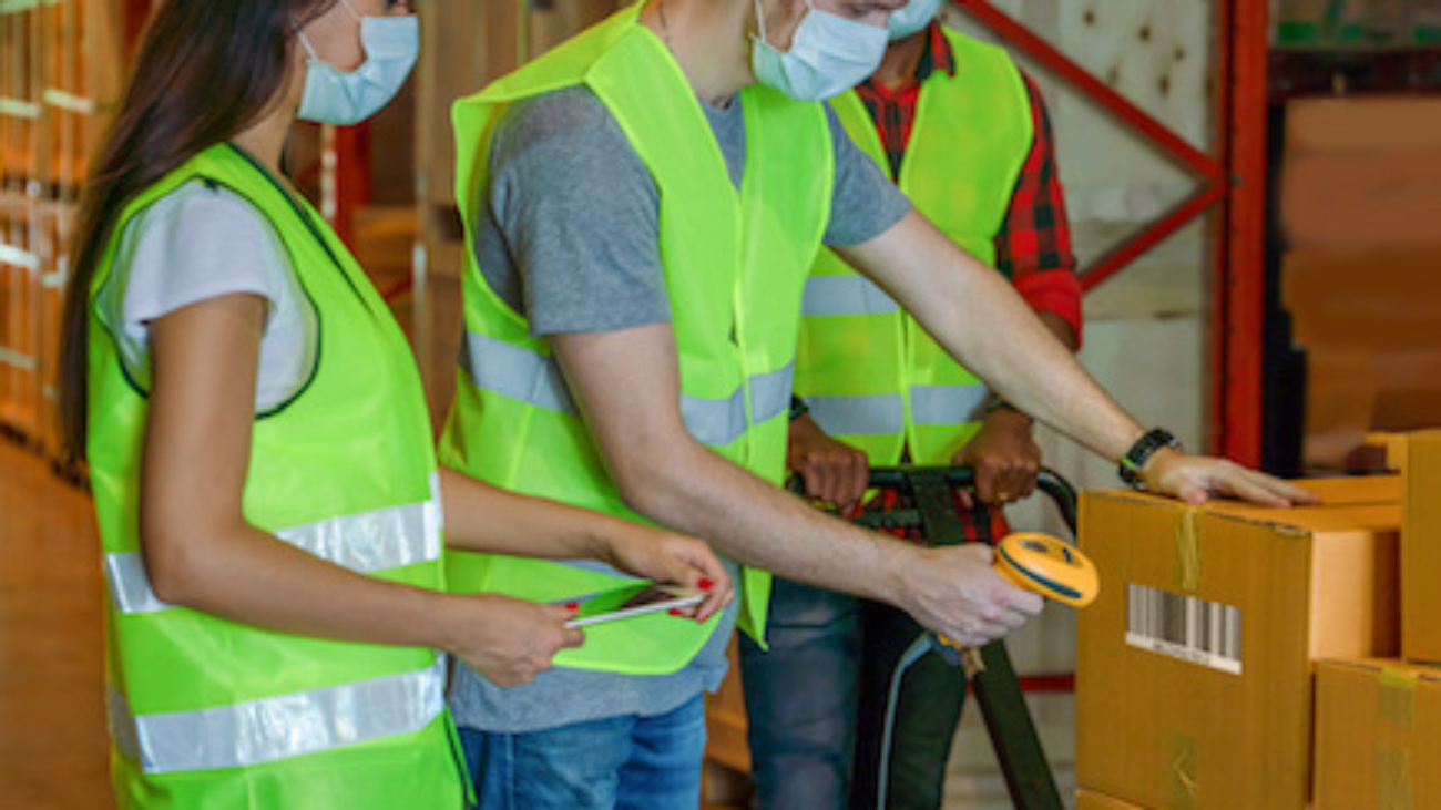 factory warehouse workers wearing face mask scanning barcode